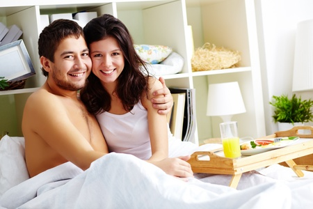 A young man embracing his girlfriend while sitting in bed in the morning Stock Photo - 12008973