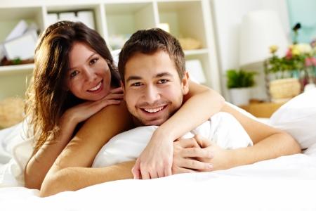 enamorados en la cama: Joven pareja feliz en la cama y mirando a la cámara