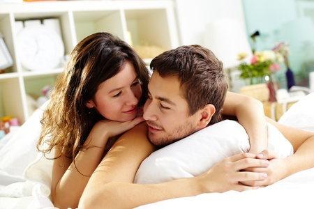 lovers in bed: Happy young couple lying in bed and looking at one another Stock Photo