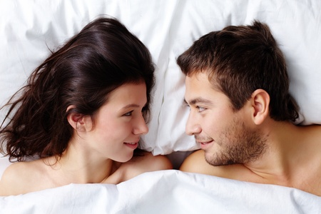 Happy young couple lying in bed and looking at one another Stock Photo - 12009003