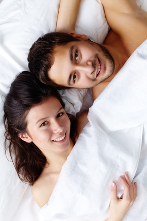 a pair of: Happy young couple lying in bed and looking at camera