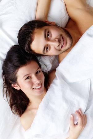 intymno: Szczęśliwa młoda para w łóżku i patrząc na kamery
