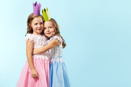 Portrait of smart girls in beautiful dresses and crowns photo