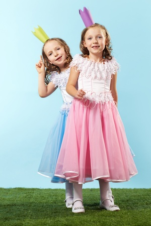 Portrait of two smart girls in beautiful dresses and crowns photo