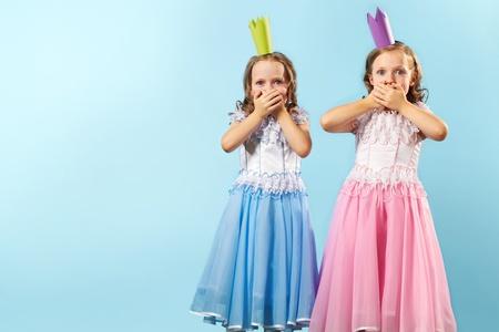 niñas gemelas: Retrato de dos niñas en hermosos vestidos y coronas que muestran su asombro