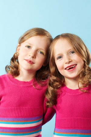Portrait of happy twins in crimson clothes against blue background Stock Photo