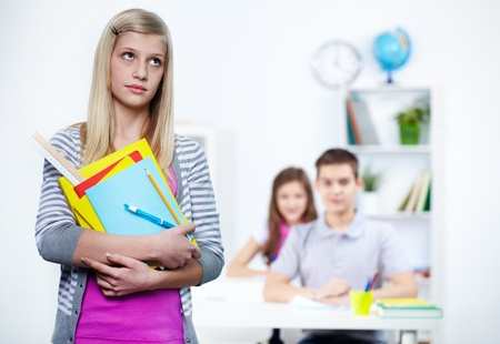 serious guy: Portrait of pensive teenage blonde with school objects Stock Photo