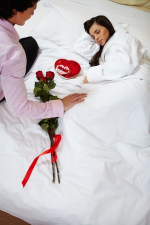 A young man looking at sleeping woman and leaving romantic present for her photo