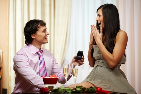 love expression: A young man giving engagement ring to his girlfriend while making her proposal Stock Photo