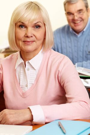 retraining: Portrait of blond female looking at camera with senior man on background