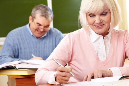 retraining: Portrait of mature female making notes in copybook with senior man on background