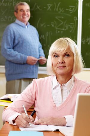 pensionary: Portrait of blond female looking at camera with senior man on background