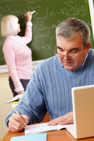 retraining: Portrait of mature man making notes on background of teacher standing by blackboard