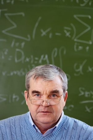 retraining: Portrait of aged teacher looking at camera with blackboard on background