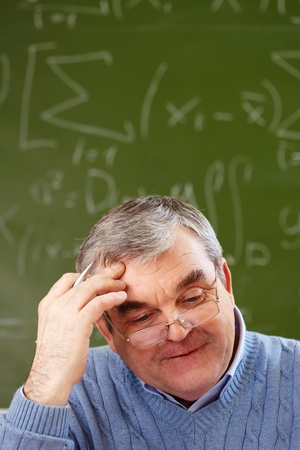 pensionary: Portrait of aged teacher thinking of idea with blackboard on background