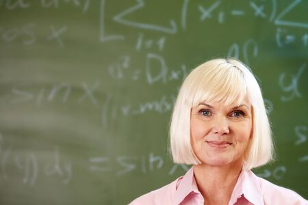 congenial: Portrait of blond female looking at camera with blackboard on background Stock Photo