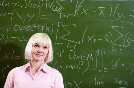 pensionary: Portrait of mature blond female looking at camera with blackboard on background