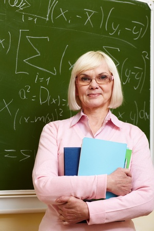 Portrait of mature teacher with copybooks looking at camera with blackboard on background photo