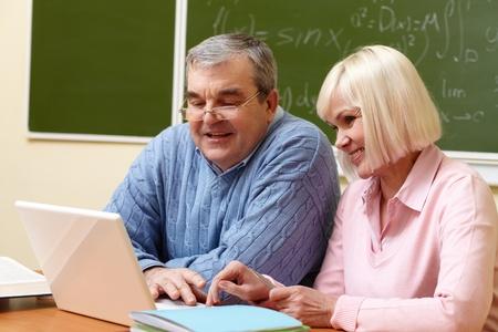 personas comunicandose: Retrato de hombre maduro y mujer trabajadora de mediana edad con ordenador portátil durante el curso de capacitación