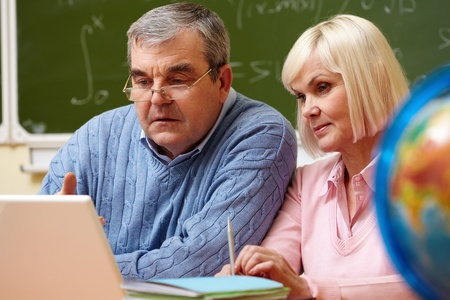 retraining: Portrait of mature man and aged female working with laptop during training course Stock Photo