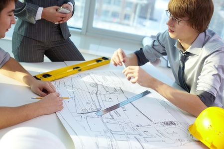 Young architect discussing new project with colleague in office photo