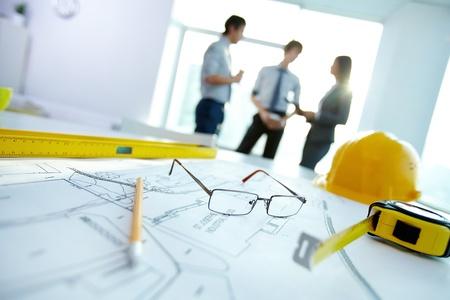 Afbeelding van engineering objecten op de werkplek met drie partners interactie op de achtergrond Stockfoto