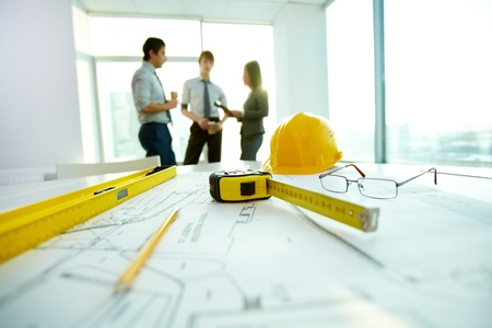 ambiente laboral: Imagen de los objetos de ingenier�a en el lugar de trabajo con tres socios que interact�an en el fondo