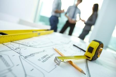 herramientas de carpinteria: Imagen de los objetos de ingeniería en el lugar de trabajo con tres arquitectos que interactúan en el fondo