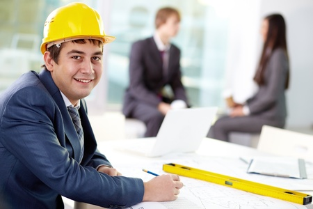 young engineer: Young engineer looking at camera with his colleagues on background Stock Photo