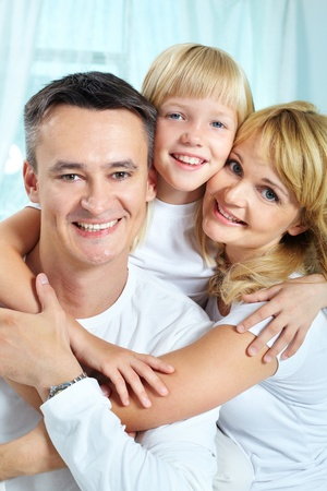 Portrait of happy parents with their daughter looking at camera at home  Stock Photo - 12057348