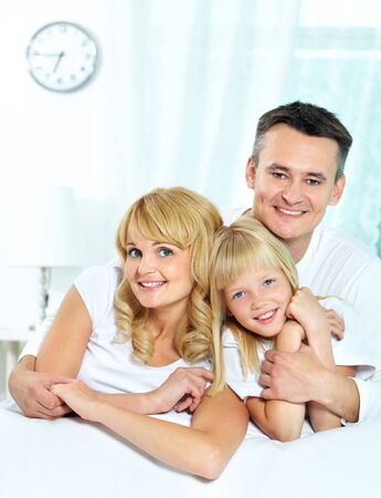 Portrait of happy parents with their daughter looking at camera  Stock Photo - 12057314