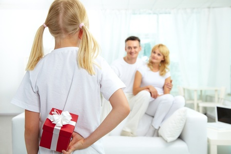 gift behind back: Back view of daughter hiding giftbox while looking at her parents  Stock Photo
