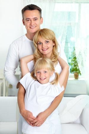 personas abrazadas: Retrato de padres felices y su hija mirando a la cámara con sonrisas