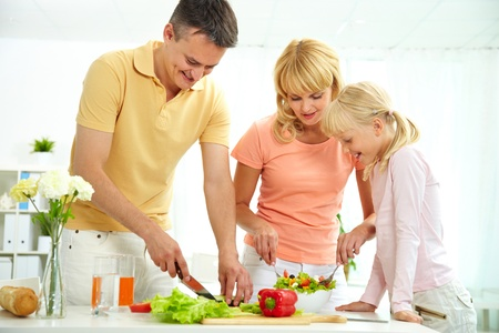 Portrait of happy parents and their daughter cooking salad in the kitchen  photo