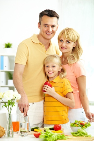Portrait of happy parents and their daughter looking at camera in the kitchen Stock Photo - 12057316