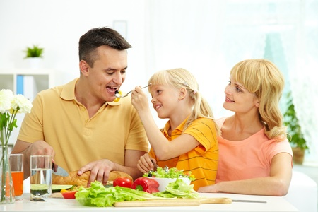 child food: Portrait of happy family having breakfast in the morning in the kitchen