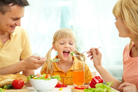 Portrait of happy parents feeding their daughter with salad in the kitchen  photo