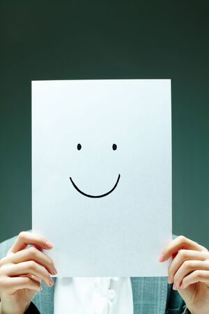 Image of female holding paper with drawn smile in front of her face photo
