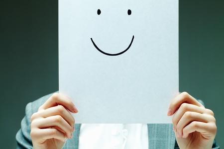 Image of female holding paper with drawn smile by her face Stock Photo - 12061639