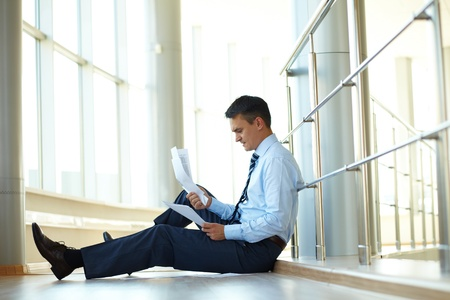 Portrait of nervous businessman sitting on the floor with papers photo