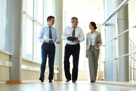 modern business lady: Confident business partners walking down in office building and discussing work