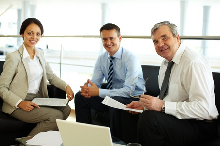associates: Portrait of happy team looking at camera at workplace
