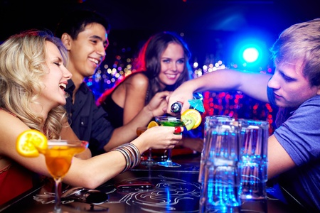 bar: Image of happy girl looking at her glass while young man pouring cocktail into it with friends near by