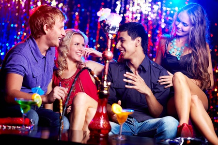 Image of two happy couples interacting in night club photo