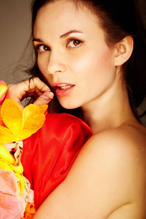 Gorgeous woman with flower and red silk looking at camera photo