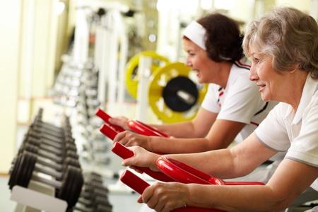 Two senior women exercising on training machines  Stock Photo - 12324466