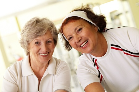 Portrait of two cheerful grandmas looking at camera with smiles  photo