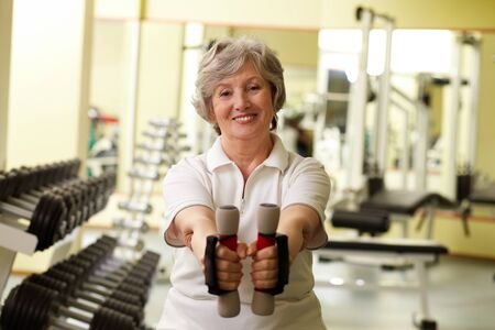 elderly exercise: Portrait of pretty senior woman exercising with dumbbells