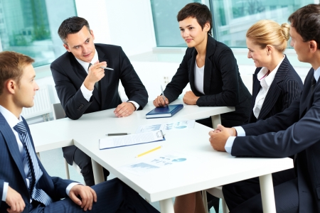 Image of confident colleagues communicating with their boss at meeting photo