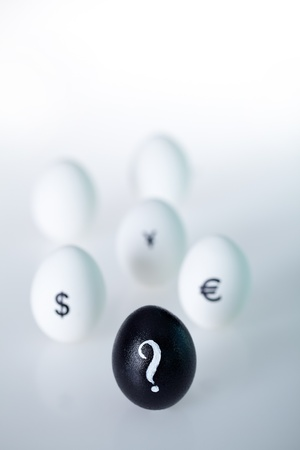 Close-up of black egg with question mark on it on background of white eggs photo